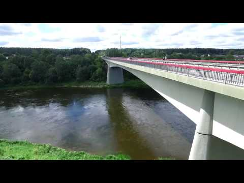 Flying Away From The Bridge Near River And Small Town In Distance - cutestockfootage.com