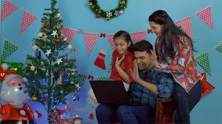 Small happy family of three doing video call with relatives and friends on Christmas