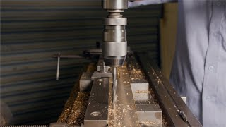Shot of a worker drilling a metal plate and changing drill bit