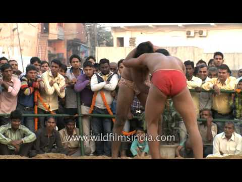 Wrestlers grabble their counterpart during a Kushti competition in India