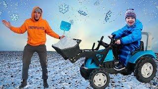 Малыш на синем тракторе с ковшом помогает папе и убирает снег