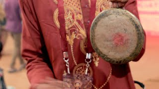 An artist playing an instrument (drums) during durga pooja
