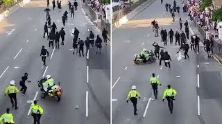 Hong Kong police officer drives motorcycle into protesters