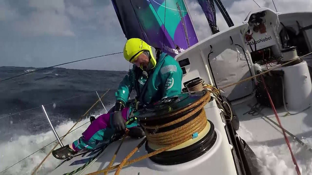 Drone shot tracking behind them as they sail fast. Wake. Rudders. Slomo washing machine in the cockpit. Spreader cam. Stacking.