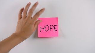 "Closeup shot of woman's hand sticking note with ""Hope"" text on a white wall"