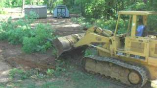 Clearing brush with the 953B trackloader for our garage