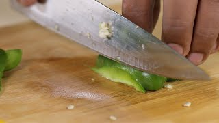 Close up shot of a man slicing green capsicum