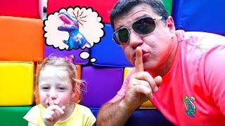 Nastya và cha cô giả vờ chơi với con khủng long khổng lồ
