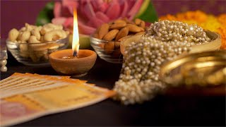 Pan shot of Indian currency / money, jewellery, diya and dry fruits decorated for diwali festival