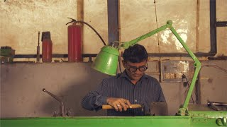 A serious Indian worker is working on a lathe machine