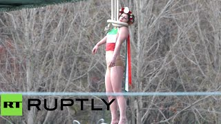Topless FEMEN 'hangs' herself on Paris bridge to protest Rouhani's visit