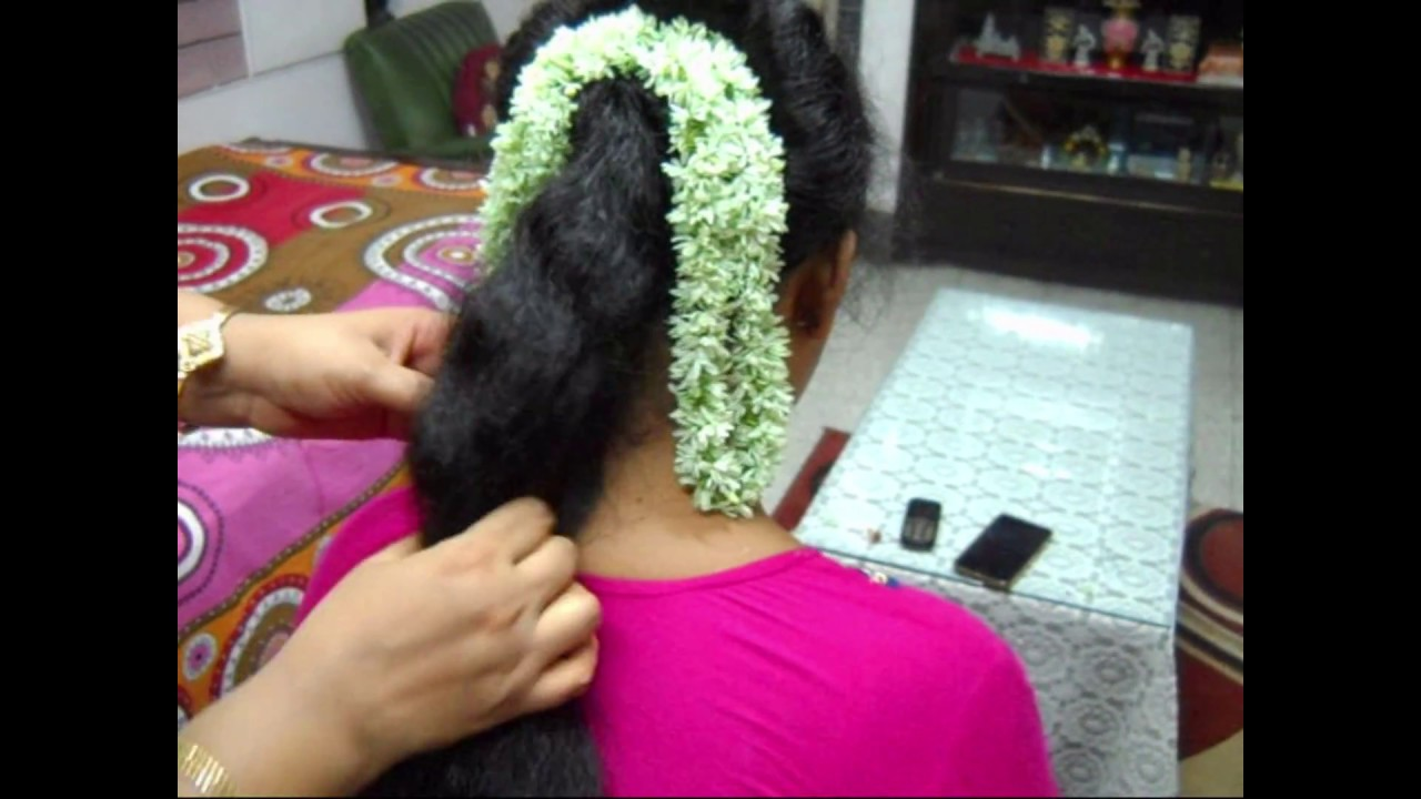a traditional hairstyle with jasmine flowers. indian hairstyles.