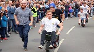 Competitors Race around Town in Mass Wheelbarrow Race