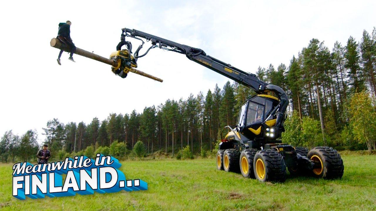 Verrückte Finnen reiten auf einer Baumerntemaschine