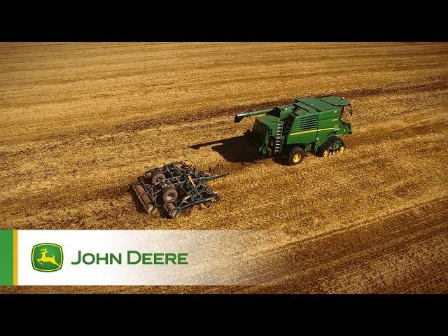 John Deere T670 Combine pulling a disc harrow while harvesting