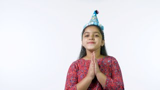 Happy Indian girl enjoying a birthday party against the white background