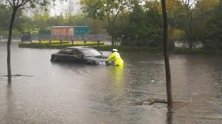 Police Officer Helps With Vehicles Trapped In N China's Flood