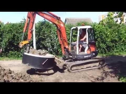 Мини экскаватор монтирует колодец из 1,5 метровых бетонных колец - steh39.ru