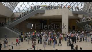 Busy underground lobby of Louvre Pyramid