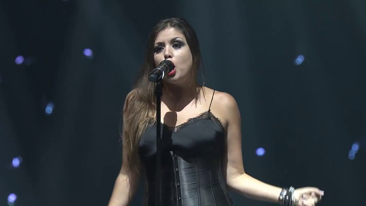 Cristina Ramos performing on the stage holding a mic in her hand
