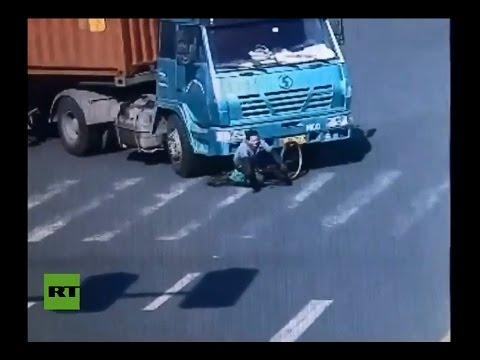 Видео: Обманувший смерть в Китае велосипедист попал под фуру и выжил