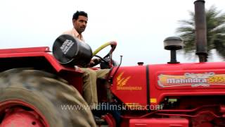 Man drives Mahindra 575 tractor through a railway check-post in North India