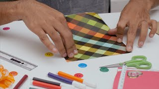 Shot of a man folding a colorful sheet of craft paper into half