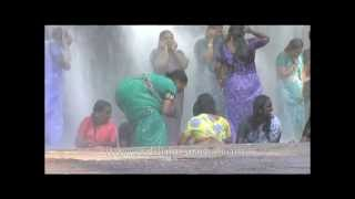 Women wearing sarees getting wet and having fun under waterfall