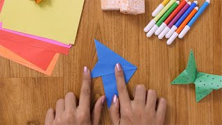 Time lapse shot of a girl making origami fish from blue craft paper