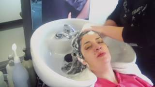 The very long black hair of a lady being washed in salon