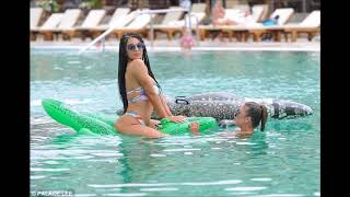 Ex Love Islander Katie Salmon straddles an inflatable crocodile as she takes to the pool