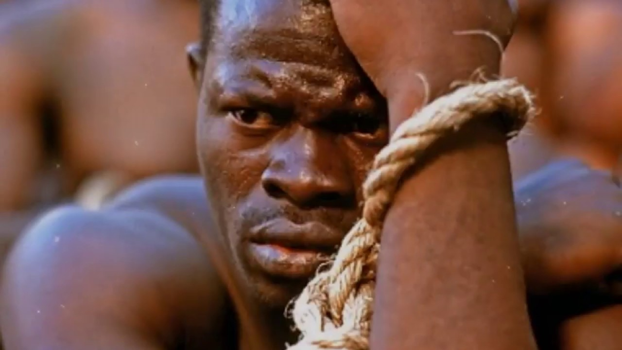 the description of the beginning of slavery and how it began in the film amistad The film begins in the depths of the schooner la amistad, a slave-ship carrying captured west africans into slavery the film's protagonist, sengbe pieh ( djimon hounsou ), most known by his mende name, cinqué (meaning fifth), painstakingly picks a nail out of the ship's structure and uses it to pick the lock on his shackles.