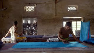 Block Printing - Two Indian men applying color to the block and presses it on the cloth