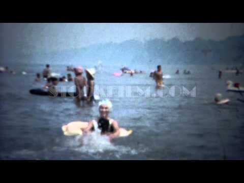 1961: Mom teaching son to swim in ocean kicking legs hard. TOKYO, JAPAN