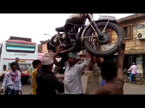 man carrying bike(royal enfield) on head and climbing the ladder