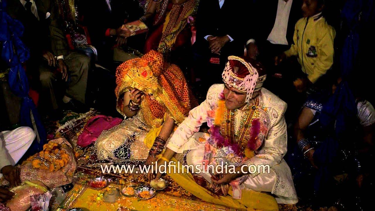 Groom and bride feed each other a sweet : Kumaoni wedding