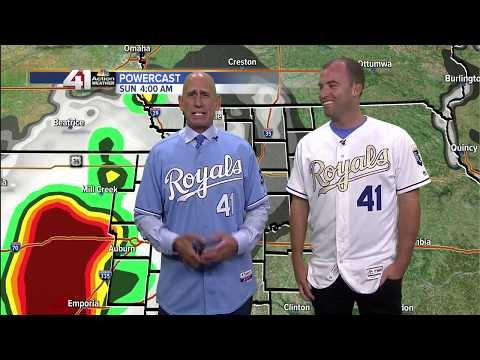 Kansas City Royals pitcher Danny Duffy helps Gary Lezak during weather