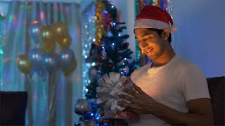 Smiling man in Santa Claus hat opening a surprise gift box on Christmas in India