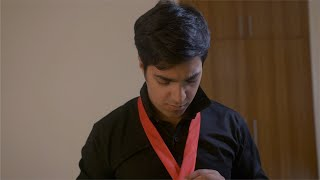 Young Indian businessman putting on a red tie. Getting ready for work