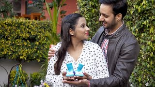 Pregnant Indian couple holding a pair of baby's blue socks during the final trimester