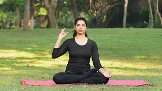 A young girl doing nadishodhana / anulom vilom / alternate nostril breathing pranayama in a park