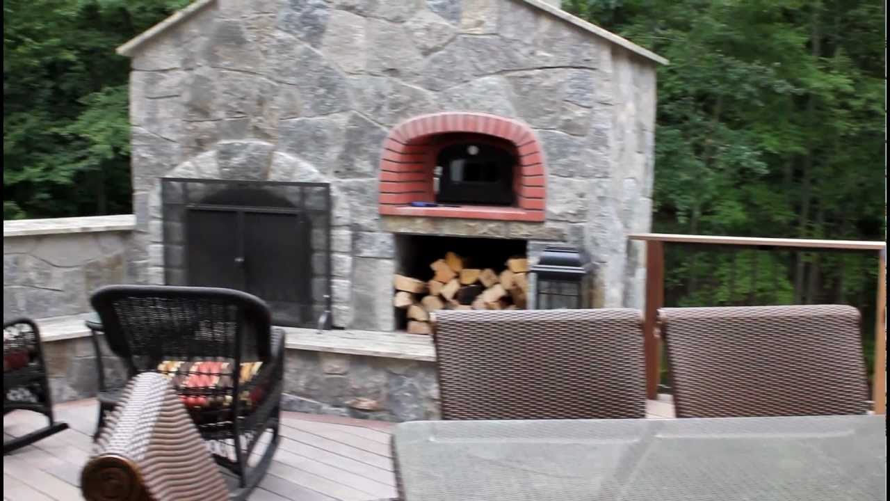 outdoor kitchen and stone fireplace with pizza oven built into this