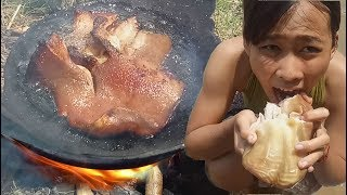 cooking in forest- grilled pig ear on a rock- eating delicious