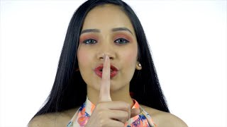 Beautiful Indian girl shushing with a finger on her lips against the white background