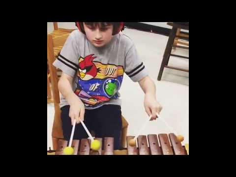 Alex using four mallets on the marimba (xylophone)!- Music Therapy Session