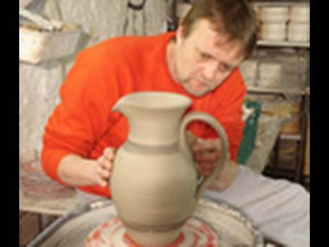 Throwing making a big clay pottery Jug / Pitcher on the wheel