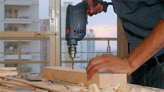 Shot of a carpenter drilling a hole in a piece of wood with a drill machine