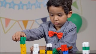 Little boy playing with colorful building blocks in a serious mood