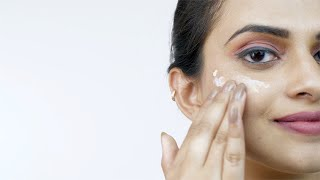 Closeup of a Indian woman applying foundation to her face against white background