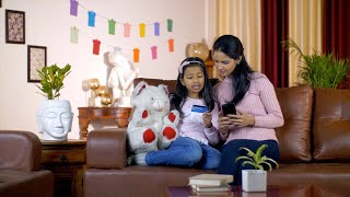Pretty Indian mother and daughter doing card payment using a smartphone in India